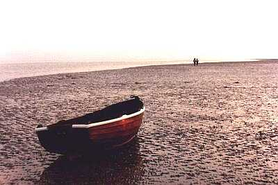 Rowing boat and distant couple, Worthing beach, Sussex